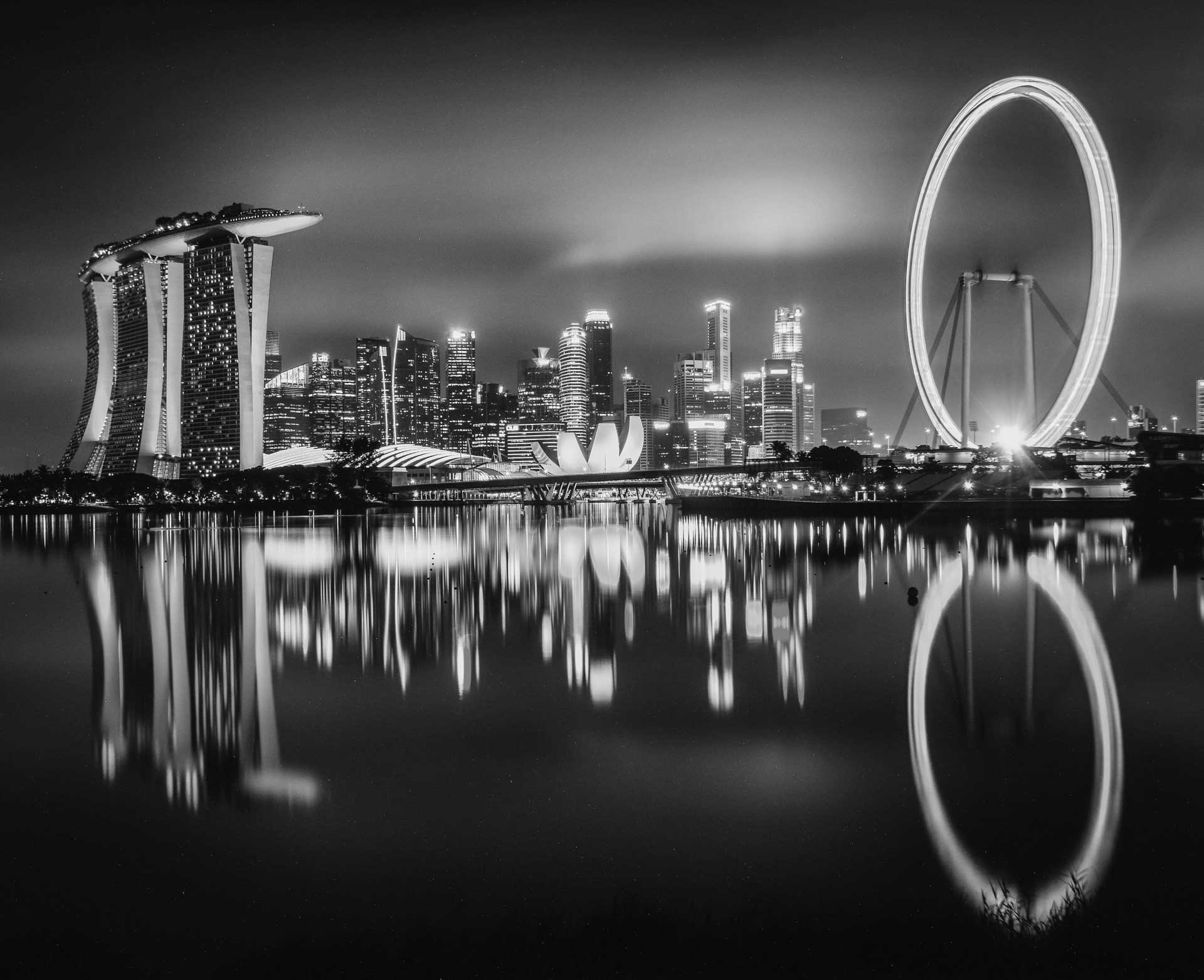 Black-and-white photo of Singapore with Marina Bay Sands on the left and the Singapore Flyer giant ferris wheel to the right