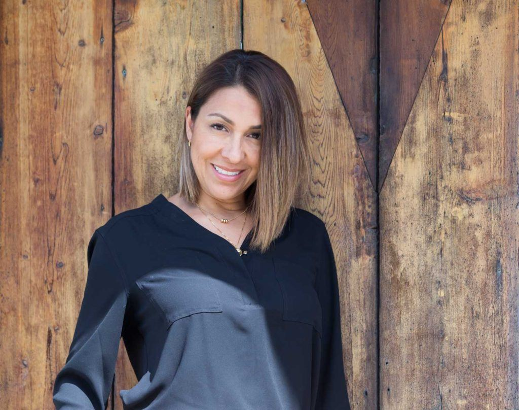 Headshot of Alma Zaleta standing in front of wooden wall